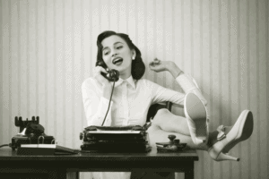 a sepia toned picture of a woman on an old phone with her legs up on the desk and a typewriting in front of her