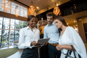 three employees smiling and gathering to look over one tablet in a hotel lobby
