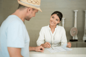 a woman employee smiling and showing a man in a hat something on a piece of paper from behind a hotel desk