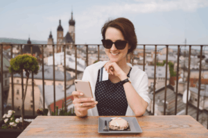 a woman in sunglasses wearing a black dress with polka dots smiling at her smartphone with a payment card in her hand sitting on a rooftop restaurant