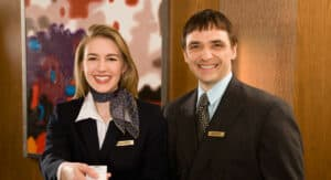 a woman wearing a black suit and neck scarf holding out a hotel key next to a hotel manager in a suit, both smiling and looking at the camera