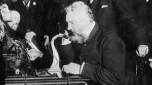 Black and white photo of Alexander Graham Bell using a phone