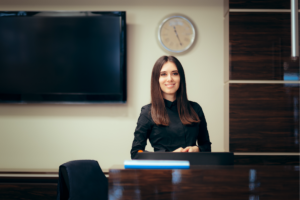 women wearing a black long sleeve top behind a hotel desk smiling at the camera