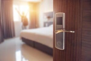 close shot of a silver hotel door handle with the hotel room in the background
