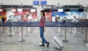 women walking through airport with face mask on