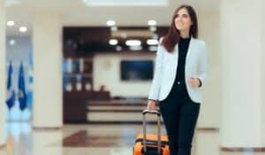 Women walking with suitcase through hotel smiling