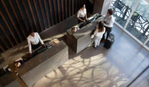 arial photo of two people checking into a hotel with two employees behind the desk with stone desks, a window showing the street outside and wood accents on the wall