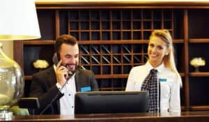 two hotel receptionists at desk, one on the phone
