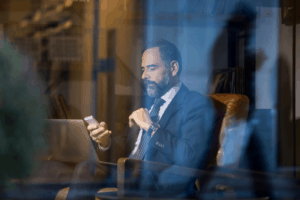 a man sitting and using his smartphone and laptop inside a hotel