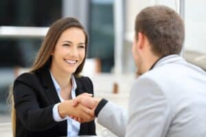 woman smiling and wearing a black suit and blue top shaking hands with a man in a grey suit