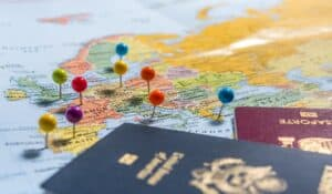 colorful pins in world map next to two passports