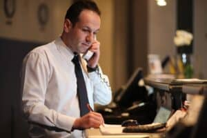 man in a white dress shirt and black tie on the phone behind a hotel desk