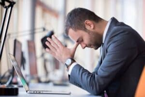 Man wearing gray suit expressing stress and regret while sitting in front of a laptop