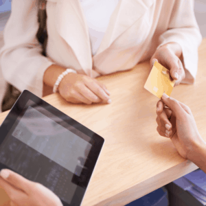 close up of a woman handing a hotel employee a gold credit card to use with a tablet