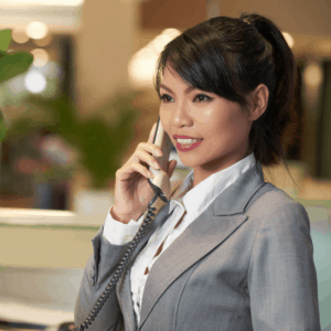 a woman employee wearing a light grey suit, talking on the phone
