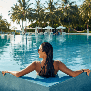 a woman with long hair in the corner of a pool facing away from the camera with lounge chairs and umbrellas in the background and palm trees as well