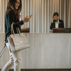 a woman smiling at her smartphone while rolling a suitcase through a hotel lobby with a hotel employee behind a desk in the background