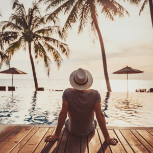 person in a hat facing away from the camera, feet dangling into an infinity pool with an ocean and palm trees in the background