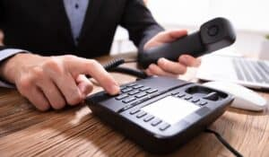 person typing in phone number on a landline phone