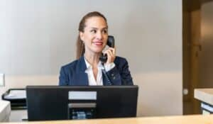 female hotel receptionist at front desk on phone