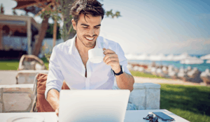 man drinking coffee outside while working on his computer