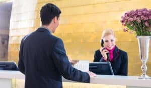 Female hotel receptionist on phone while looking at computer screen while man waits in front