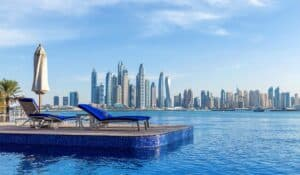 luxury pool hotel with blue cushioned lounge chairs and a city skyline in the background