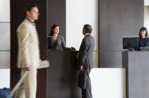 a man in a suit facing a hotel employee behind a desk near another employee looking at a computer and a man in motion passing by