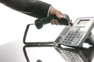 a hand holding on a landline phone while also pressing down the end call button