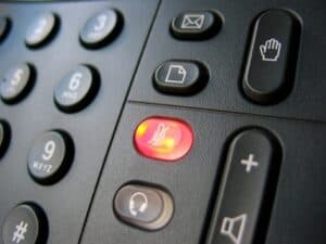 close up of a landline showing a red lit mute button
