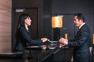 a hotel employee in a suit handing a man a piece of paper from the other side of the hotel desk