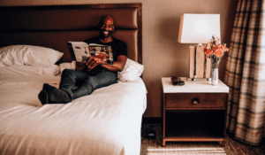 Man sitting on hotel bed reading magazine
