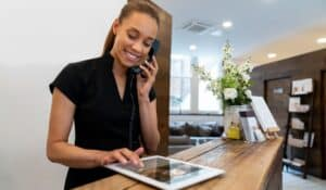 Female hotel receptionist on phone and tablet