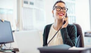 Hotel receptionist sitting at desk on phone while smiling