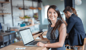 business women working on computer while looking at the camera smiling
