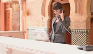 female hotel receptionist behind counter on phone