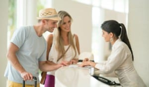 young couple checking in at reception desk in hotel