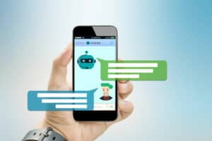 a hand holding a smartphone showing a text conversation with a chat bot and two message bubbles