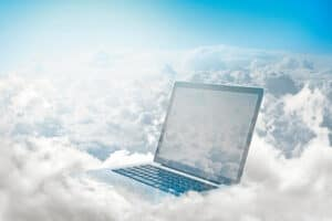 a laptop sitting on white clouds in the the middle of a sky to convey cloud computer