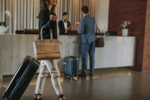 a woman holding a purse and a suitcase walking through a hotel lobby with the hotel concierge in the background
