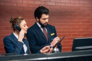 two hotel employees wearing suits with one on the phone and one writing things down behind a hotel desk with a brick wall in the background
