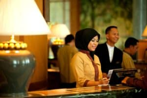 woman hotel employee smiling while looking at a computer behind a hotel desk