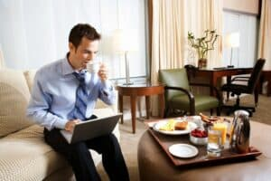 a man wearing a blue shirt drinking coffee and using a laptop while sitting on a couch near an ottoman with breakfast sitting on it in a hotel room