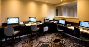 a business center in a hotel room with four computer monitors and a print machine