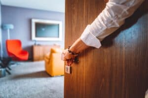 a close up of a hand opening a wooden hotel door with a hotel room out of focus in the back