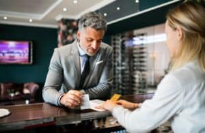 a man with gray hair and a light gray suit receiving paper from a hotel concierge over a hotel desk