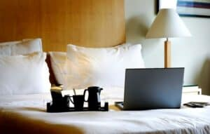 a gray laptop and black modern tea set sitting on a hotel bed