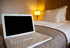 a laptop with a black screen sitting on a hotel room bed with a lamp on in the background