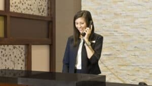 woman employee smiling and talking on the phone behind a hotel front desk with a stone wall in the background