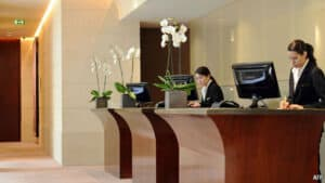 wooden hotel front desk with two female employees in suits working, orchids on the desks